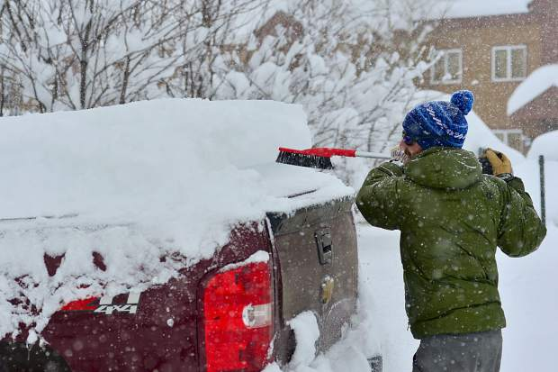 Mark Goldberger brushes a blanket of snow off his pickup truck Sunday in downtown Frisco. Across the county, people were reporting over a foot of new snow with heavy snowfall continuing throughout the day.
