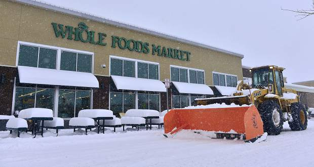 Snow is cleared from the parking lot at Whole Foods Market in Frisco on Sunday as piles remain on nearby picnic benches.