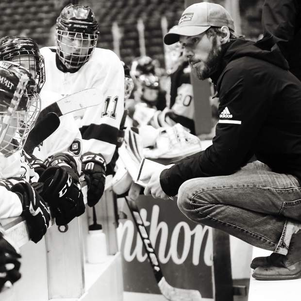Summit Youth Hockey head coach Chris Miller, right, speaks to members of the program's Bantam A team during game action earlier this season.