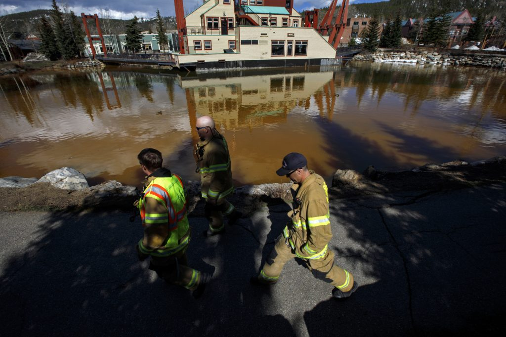 Red, White, and Blue Fire Department firefighters walk past Dredge Pond and the Blue River in Breckenridge on Saturday afternoon, April 27.