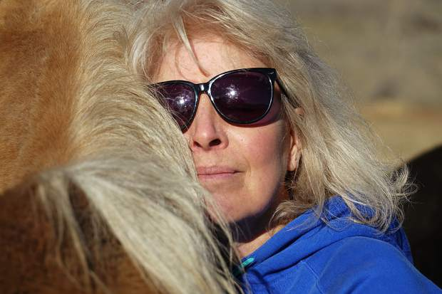 """Volunteer Karen Johns gives a horse some love at the Blue River Horse Center about 20 miles north of Silverthorne. As the center gets ready for another summer season, Johns said the work she sees there is """"truly magical."""""""