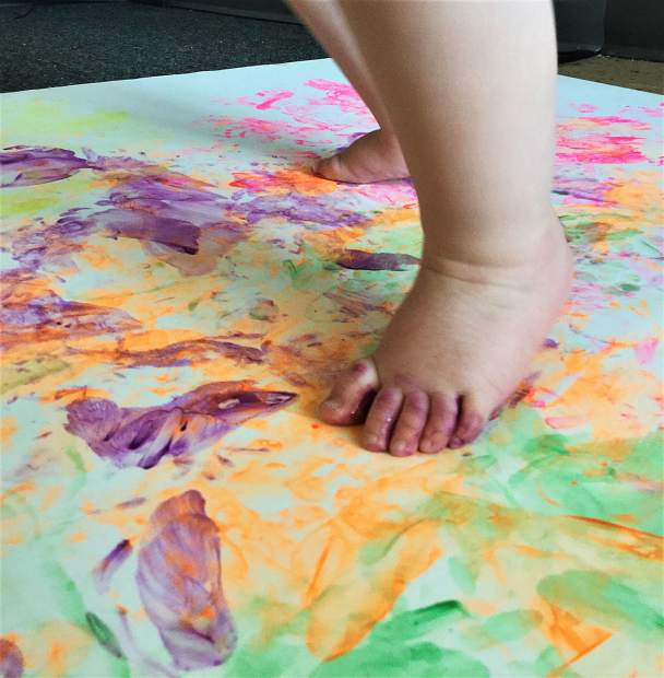 Maisie Bartelt, 4 months, uses her feet to paint a picture. Timerbline Learning Center's second annual art show opens Friday and features work from all of their students.