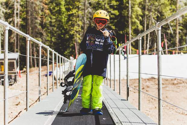 A young Woodward Copper snowboarding camper rides the 1,500-foot magic carpet lift up alongside the summer-time Pipeline Park terrain park at Copper Mountain Resort.