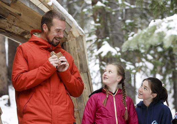 Isak Heartstone's artist Thomas Dambo, of Denmark, receives the heart-shaped stone from the Breckenridge girls Lexi Garner and Jade Batdorff to permanently install inside the troll Friday, May 10, in the new location in Breckenridge.