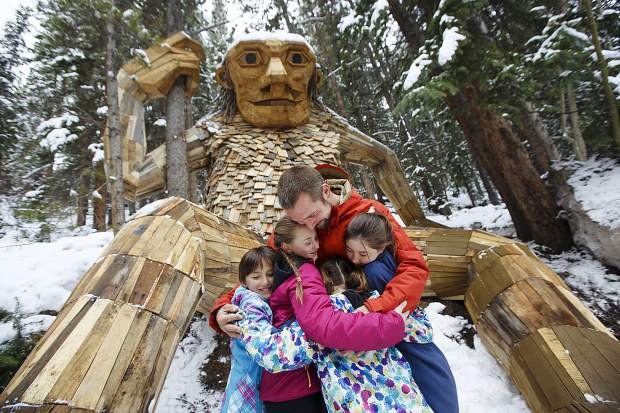 Isak Heartstone's artist Thomas Dambo, of Denmark, hugs Tori and Lexi Garner, and Jade and Paige Batdorff, who found the heart-shaped stone last summer Friday, May 10, at the troll's new location in Breckenridge.