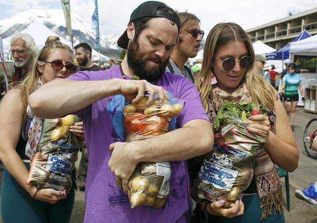 Breckenridge residents Wes Contro, center, and Cherise Gary, right, pick up fresh produce from the Dillon Farmers Market Friday, June 7, in Dillon.