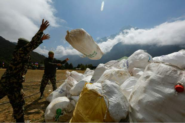 In this May 27 photo, Nepalese army men pile up the garbage collected from Mount Everest in Namche Bajar, Solukhumbu district, Nepal. The record number of climbers on Mount Everest this season has left a cleanup crew grappling with how to clear away everything from abandoned tents to human waste that threatens drinking water.