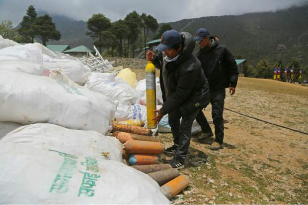 In this May 27 photo, members of garbage retrieval expedition pile up empty oxygen cylinders collected from Mount Everest in Namche Bajar, Solukhumbu district, Nepal. The record number of climbers on Mount Everest this season has left a cleanup crew grappling with how to clear away everything from abandoned tents to human waste that threatens drinking water.