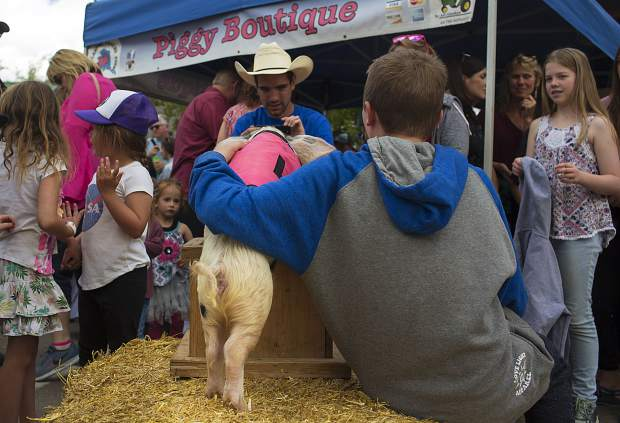 An All-Alaskan Racing Pig poses for a photo with fans following a race Saturday June 15, on Main Street in Frisco.