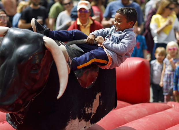 Christopher Strong, 7, hangs on to a bucking bull Saturday June 15, during the 26th Annual Colorado BBQ Challenge in Frisco.