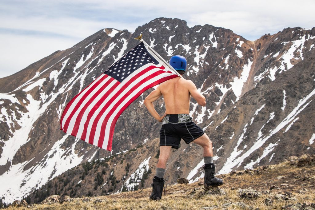A shirtless snowboarder stands with the American flag, the East Wall of Arapahoe Basin Ski Area in the distance.
