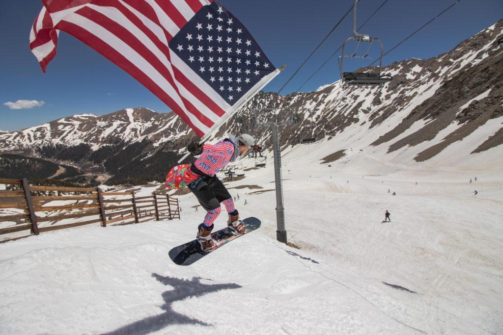 A snowboarder holds Old Glory high while riding from the top of the Lenawee lift at Arapahoe Basin Ski Area in honor of Independence Day.