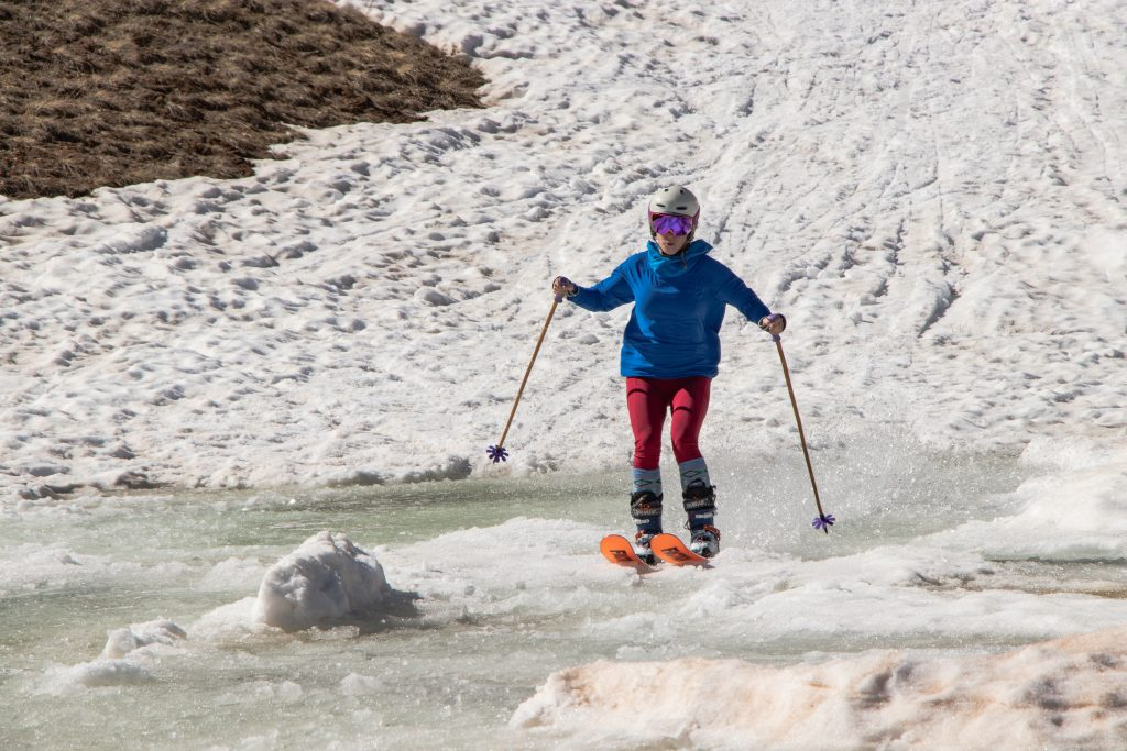 A skier keeps her tips up as she plunges into the Lake Reveal pond skim at Arapahoe Basin Ski Area on Thursday, July 4.