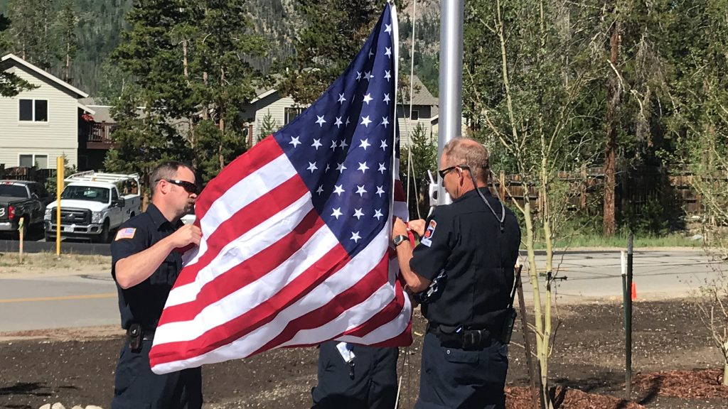 Representatives with Summit Fire & EMS raise the American and Colorado flags for the first time over the new administration building July 18, 2019.