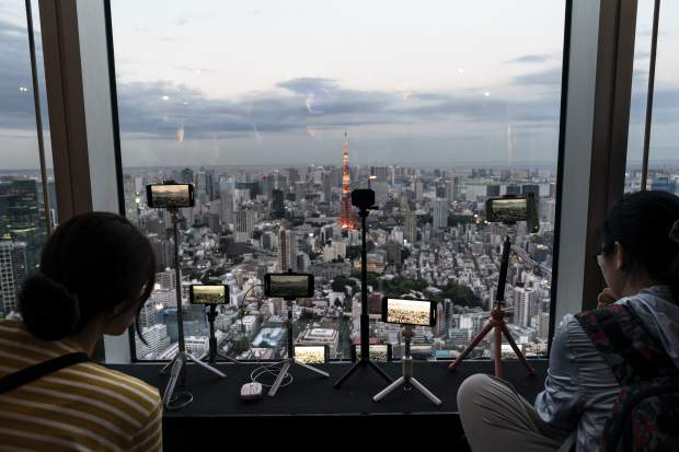 Smartphones are propped on tripods in the observation deck of the Mori Tower to capture Tokyo's skyline view in Tokyo, June 17, 2019. (AP Photo/Jae C. Hong)