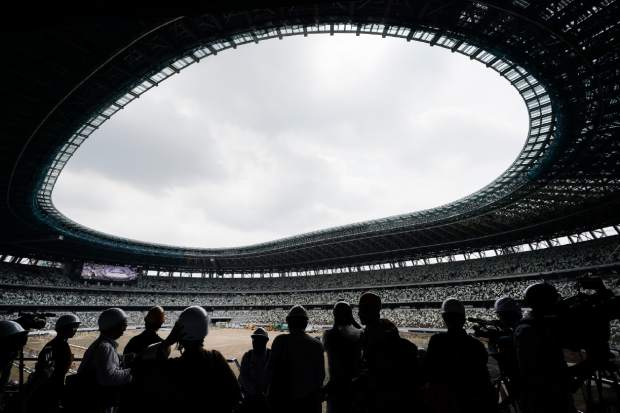 FILE - In this July 3, 2019, file photo, media tour the New National Stadium in Tokyo. Scandals and rising costs have not deterred interest in Japan in the Tokyo Olympic. They open in a year with unprecedented ticket demand. (AP Photo/Jae C. Hong, File)