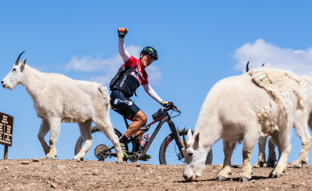 A mountain biker raises his first while pedaling past mountain goats while riding on the above-tree line terrain on the slopes of Mount Guyot during Tuesday's third stage of the 2019 Breck Epic multi-stage 6-day mountain bike race.