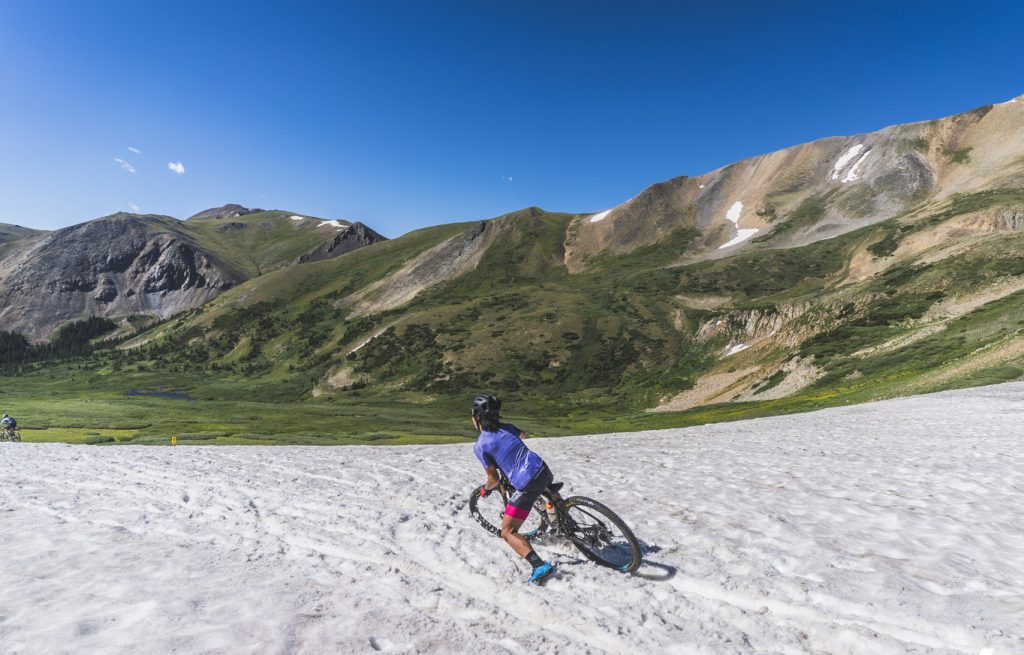 A mountain biker slipes and slides while negotiating a path through a lingering snowfield on the above-tree line slopes of Mount Guyot during Tuesday's third stage of the 2019 Breck Epic multi-stage, 6-day mountain bike race.