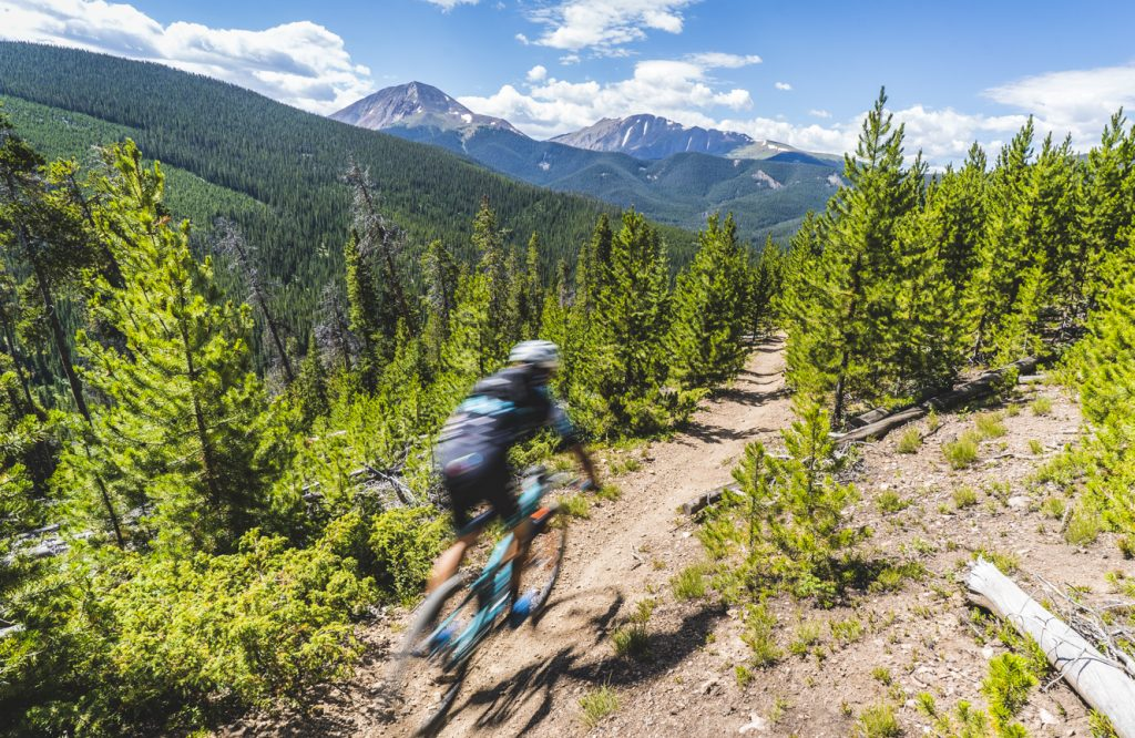 A mountain biker rides during the fourth stage of this year's 6-day Breck Epic mountain bike race, the 41-mile Aqueduct, Mounts Guyot and Baldy in view in the background.